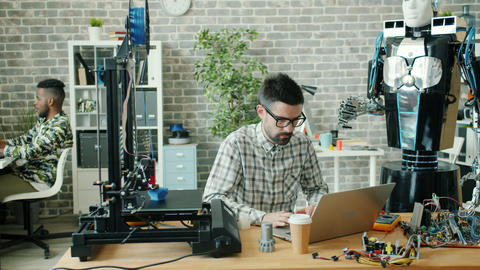 Young developer using laptop typing in office, 3d printer and robot are visible Live Action