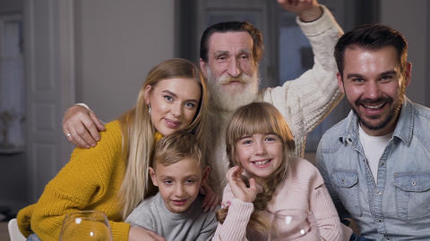 Happy bearded man hugging all his attractive joyful family and looking at camera Footage