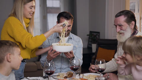 Happy cheerful mother putting spaghetti on grandfather's plate during family ビデオ