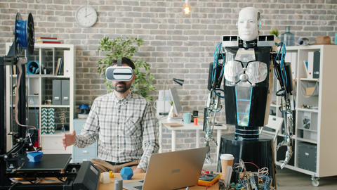 Scientist in vr glasses testing robot in office room, machine repeating Footage