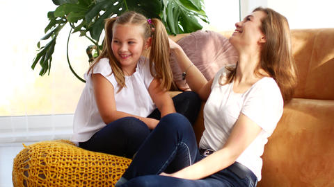 Mother and daughter communicate sitting at home on the couch. Daughter shares Archivo