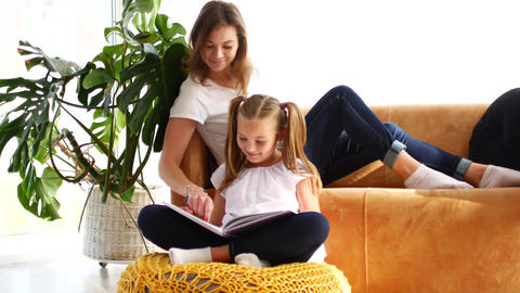 Mother and daughter are reading a book while sitting on the couch. Mom points a Archivo