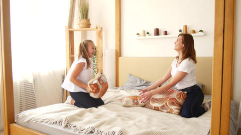 Mom and daughter throw pillows while sitting on the bed. Having fun and fooling Archivo