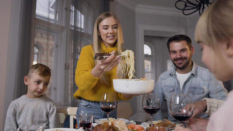 Lovely mother putting tasty spaghetti for her cute daughter during family dinner Footage