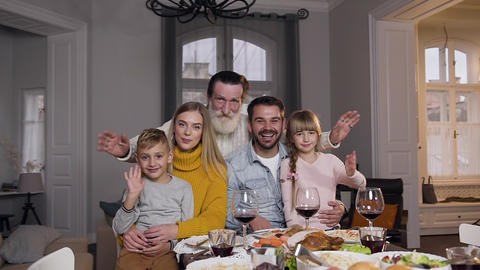 Laughing happy people-relatives sitting at the festive table and looking at Footage