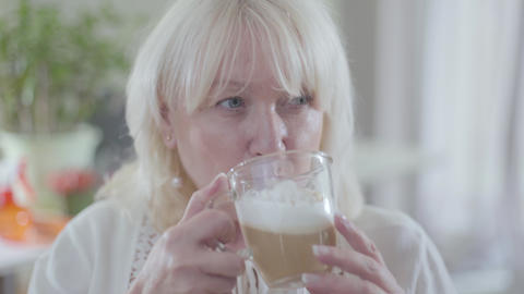 Close-up face of mature Caucasian blond woman with grey eyes drinking coffee and Archivo