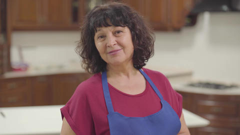 Portrait of a positive mature Caucasian woman with brown eyes and curly hair Footage