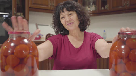 Caucasian mature woman admiring her cannings. Bottles with canned tomatos Live Action