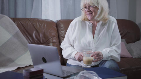 Positive Caucasian retiree sitting on sofa with coffee cup and looking at laptop Footage