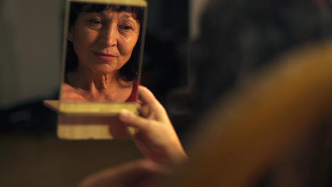 Close-up of small mirror with reflection of senior Caucasian woman fixing her Archivo