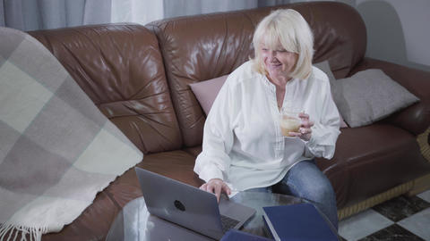 Top view of attractive senior Caucasian woman watching pictures or photos on Footage