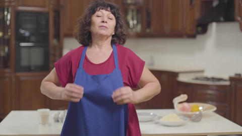 Portrait of brunette Caucasian mature woman putting on blue apron at the modern Footage