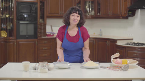 Mature Caucasian brunette woman putting two plates on the table. One plate is Footage