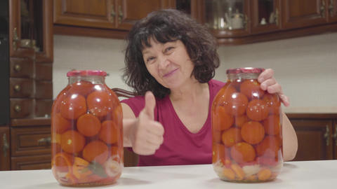 Portrait of happy Caucasian woman moving bottles with canned tomatos apart and Footage
