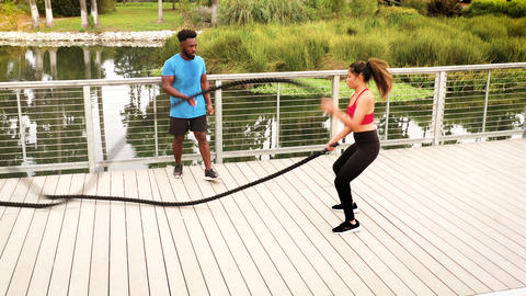 Aerial shot of a woman working out with a trainer in the park Footage