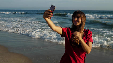 Attractive woman taking a selfie at the beach GIF