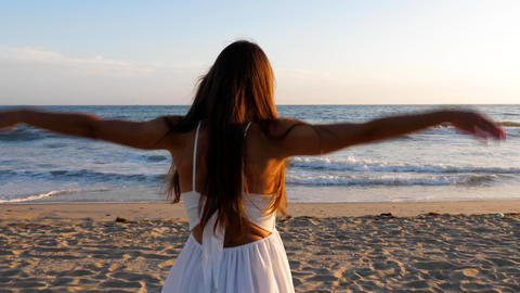 Beautiful woman in a white dress at the beach at sunset Footage