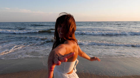 Beautiful woman in a white dress at the beach at sunset Archivo