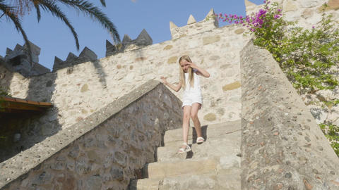 Girl walking down stairs on ancient castle GIF
