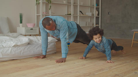 Carefree dad and son exercising push-ups at home Footage