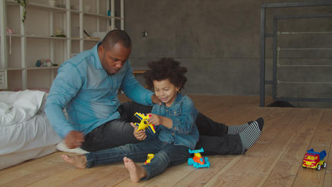 African father and son playing with toys on floor Archivo