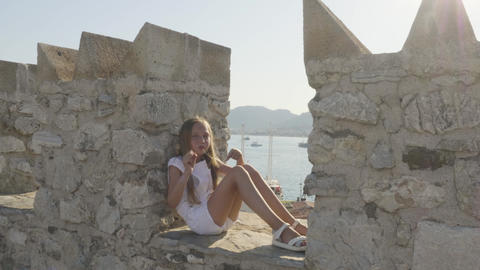 Happy girl sitting and dancing on stone wall Archivo