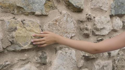 Cropped shot of human hand touching stone wall GIF