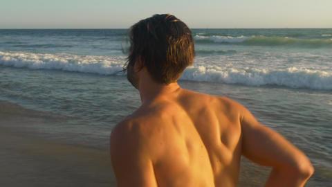Male lifeguard running along the beach Archivo