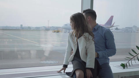 Adult Caucasian man sitting with his daughter at the airport windowsill and Footage