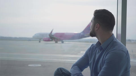 Side view close-up face of handsome bearded man looking at the airplane takeoff Footage