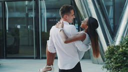 Close-up of husband holding in arms and spinning around his black wife outdoors Footage