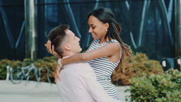Smiling multiracial couple having fun spinning around on the street Footage