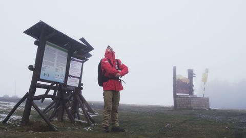 Freezing young man standing next to wooden sign on top of the mountain in dense Footage