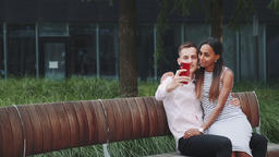 Zoom shot of beautiful mixed-race couple making selfie outdoors Footage