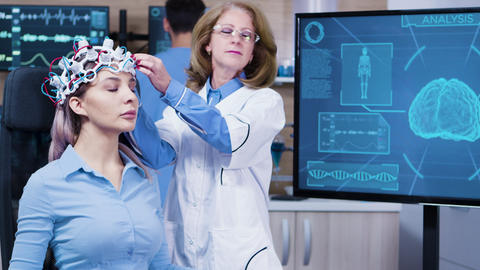 Woman wearing brain waves headset sitting on a chair Footage
