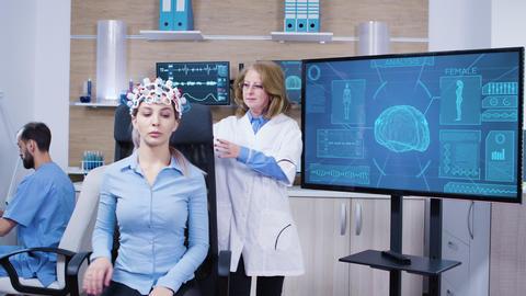 Neurology female doctor making adjustments to brainwaves headset Footage