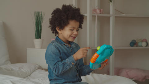 Mixed race boy playing with toy steering wheel GIF