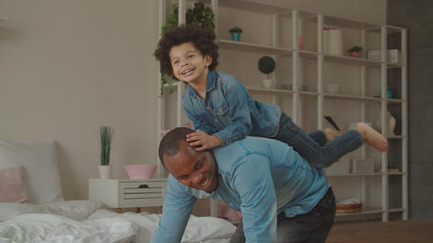 Excited son riding on black father's back at home Footage