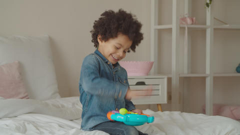 Joyful kid playing with toy steering wheel indoors Footage