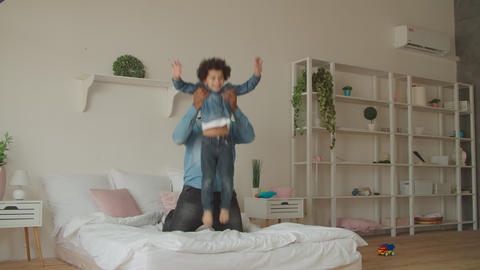 Joyful black father and little son jumping on bed Footage