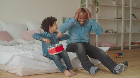 Diverse family enjoying leisure playing toy drum Footage