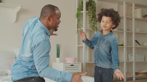 Joyful black father and cute son dancing at home GIF