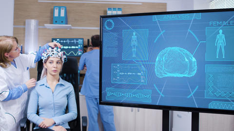 Tv screen with brain activity from female wearing brain scanner Footage