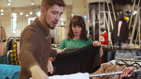 Man offers his woman a sweater and shorts in a store Footage