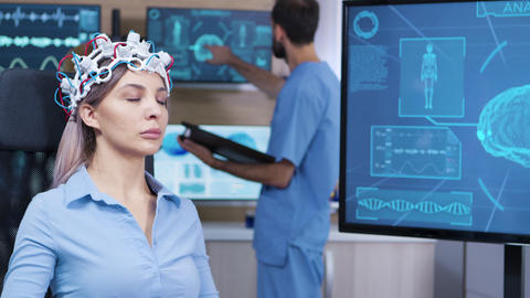 Brain activity on tv screen from female patient with brainwaves scanning headest Footage
