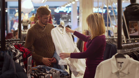 Beautiful woman chooses her man a shirt in a store Footage