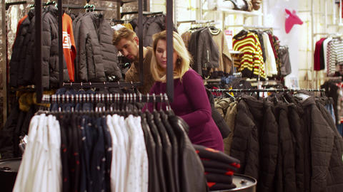 Girl helps to choose clothes for her boyfriend in the store Footage