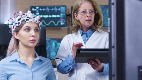 Dolly shot of female doctor checking the sensors from patient headset Footage