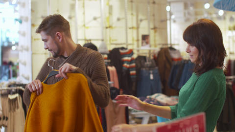 Young man chooses clothes for his woman Footage