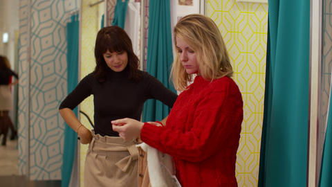 Friends in the fitting room, one girl tries on a jacket Footage